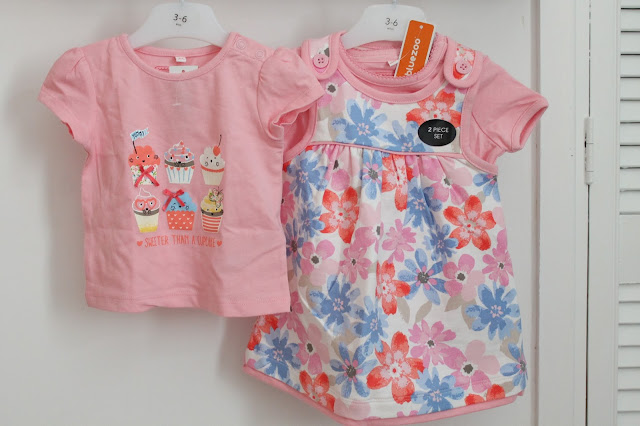 pink baby t-shirt with six cupcakes and sweeter than a cupcake text - pink vest under white pinafore with blue, pink and red flower pattern