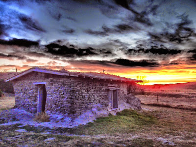 A sod house with a beautiful sunset in the background