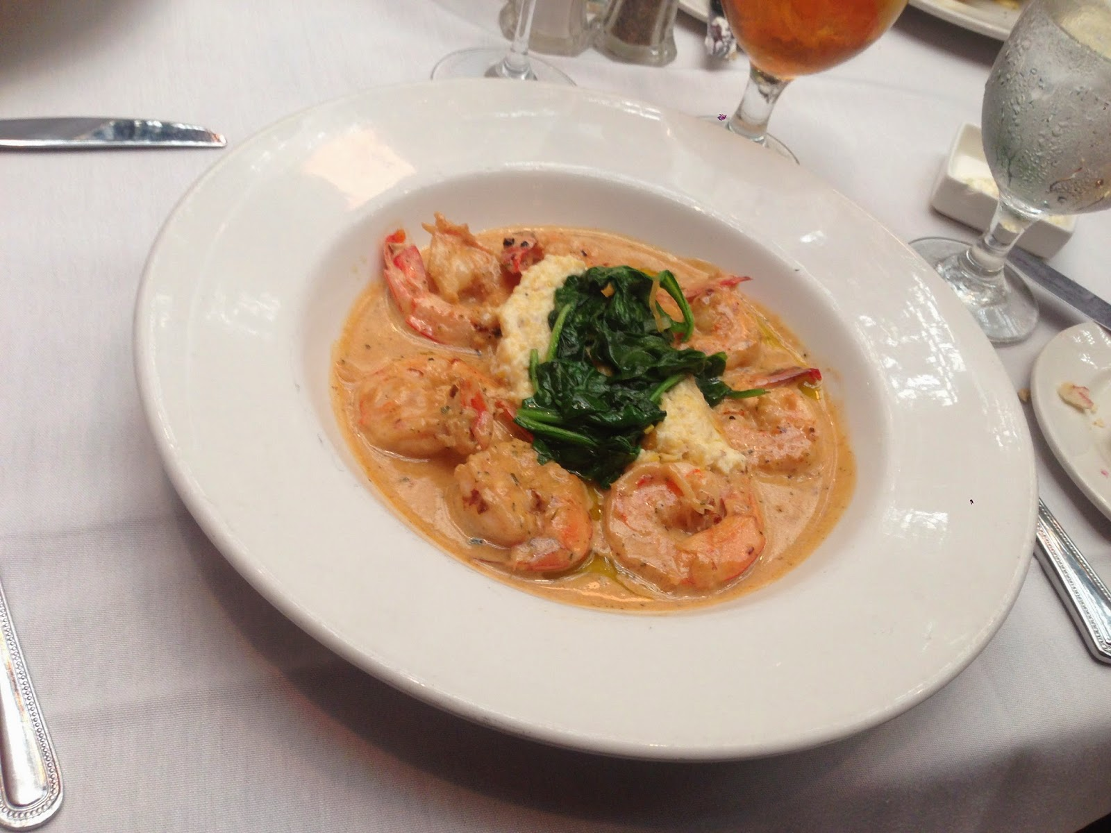 Juban's Shrimp & Grits: Gulf shrimp broiled in New Orleans barbeque butter, with garlic cheese grits,  and spinach primavera
