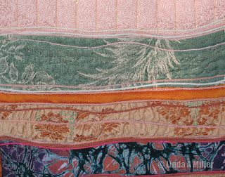 Detail of Striated quilt in aqua tans orangewith couching, embroidery