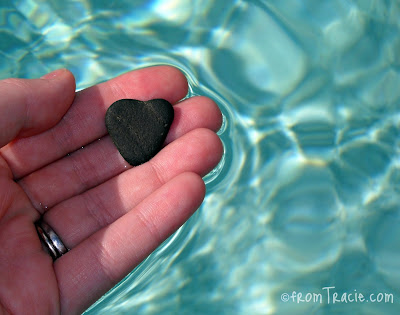 Hand Holding Heart Shaped Rock In Water