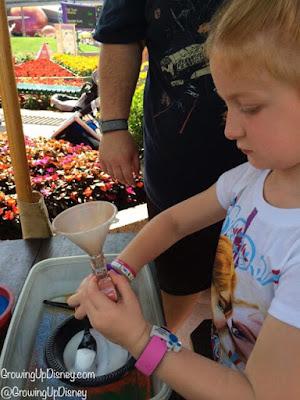 child working on sand art at Epcot International Flower and Garden Festival