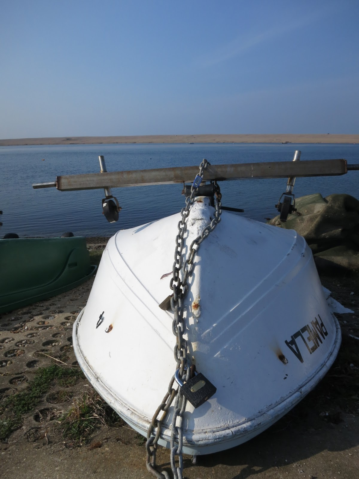 Upturned boat with chain over it and Chesil Beach in the background