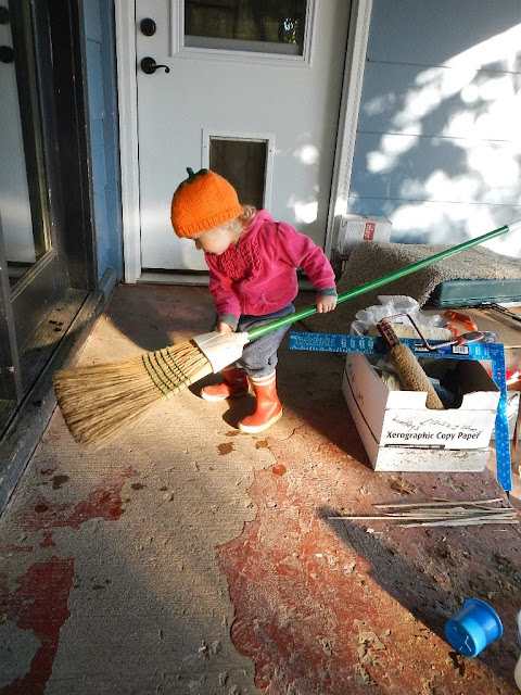 toddler helping to sweep porch