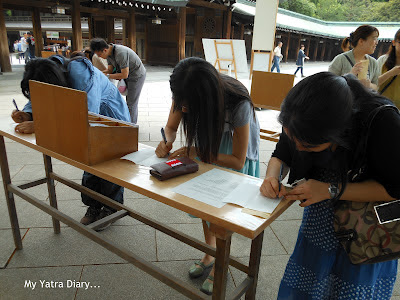 People writing prayers at the Meiji Jingu Shrine, Tokyo