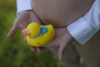 Pregnant belly holding rubber duck. Stock Photo credit: umberto