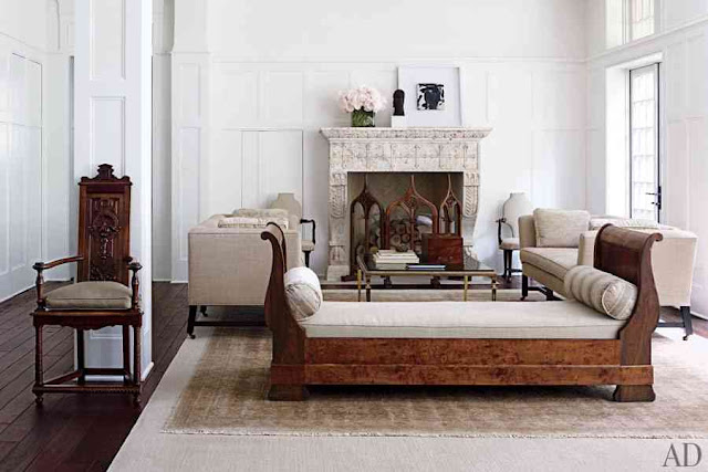 Living room with restaind wood floor and a high back bench with a white cushions, a marble fireplace and dueling sofas