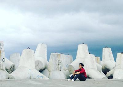 Berfoto dengan background pemecah ombak di pantai Glagah