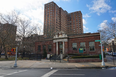 Small red brick Renaissance Revival style Library surrounded by large public housing buildings