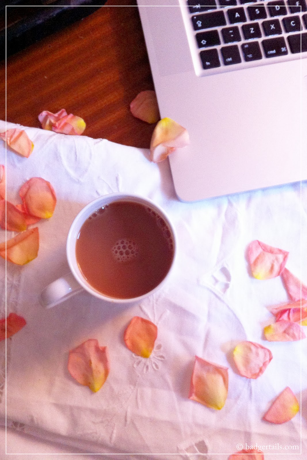 cup of tea with apple macbook pro computer laptop and rose petals on desk