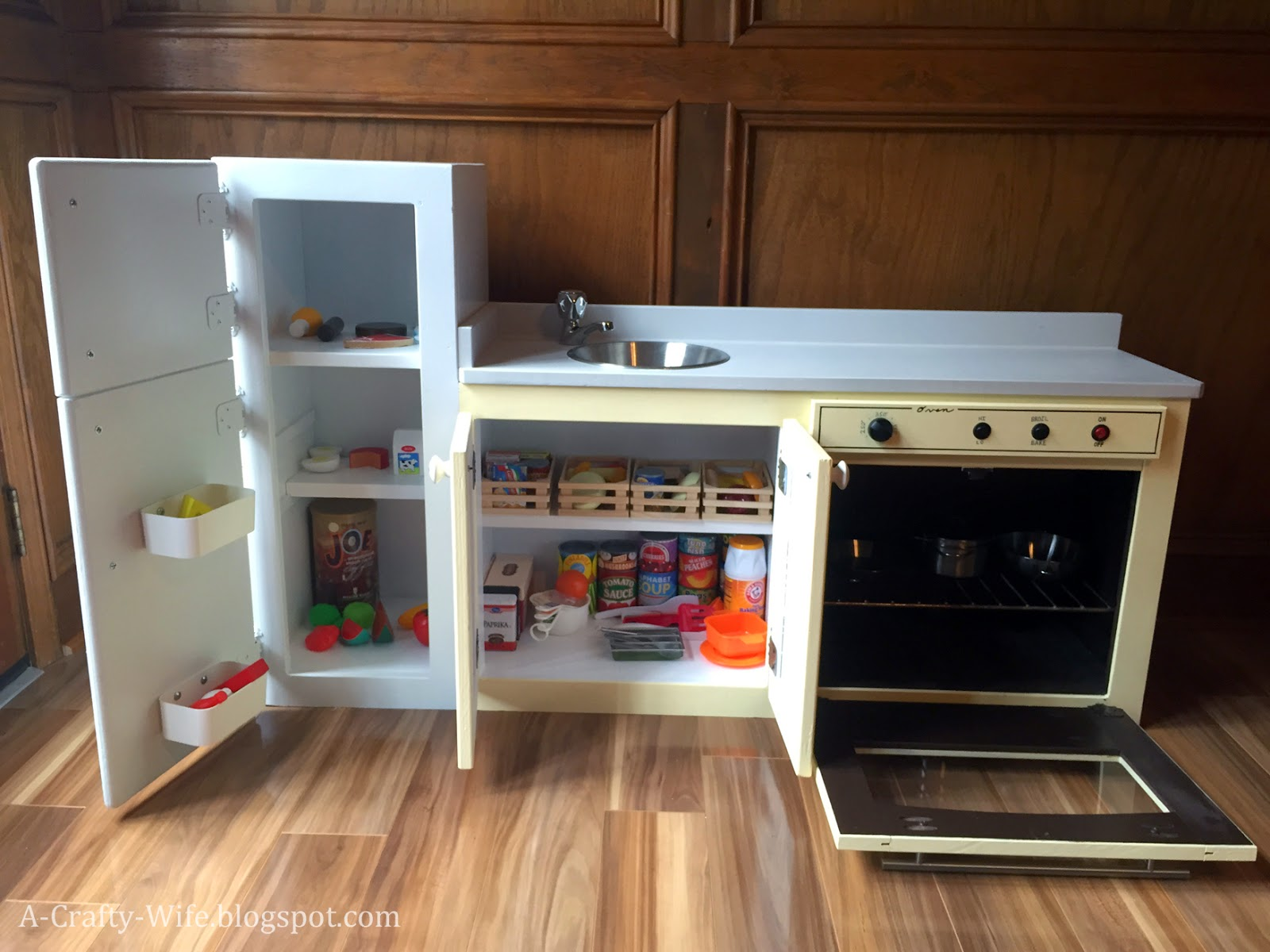 Cabinet turned into play kitchen stocked with play food from Melissa and Doug, Ikea, Toys R Us.