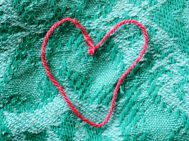 pink wool in shape of heart on green blanket