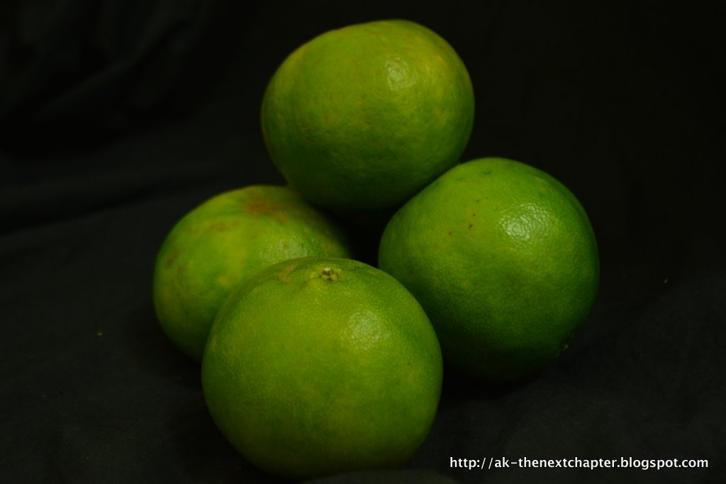 Green citrus fruits, looking like they are unripe and very sour. The colour of small lime fruit in Europe, or of very early spring leaves