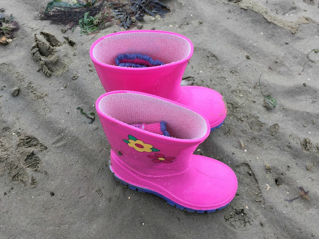 Pink wellington boots stood on wet sand