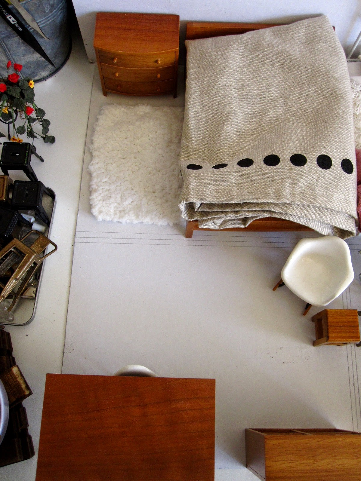 View from above of mid-century modern dolls' house miniature furniture bedroom setting arranged on a piece of cardboard.