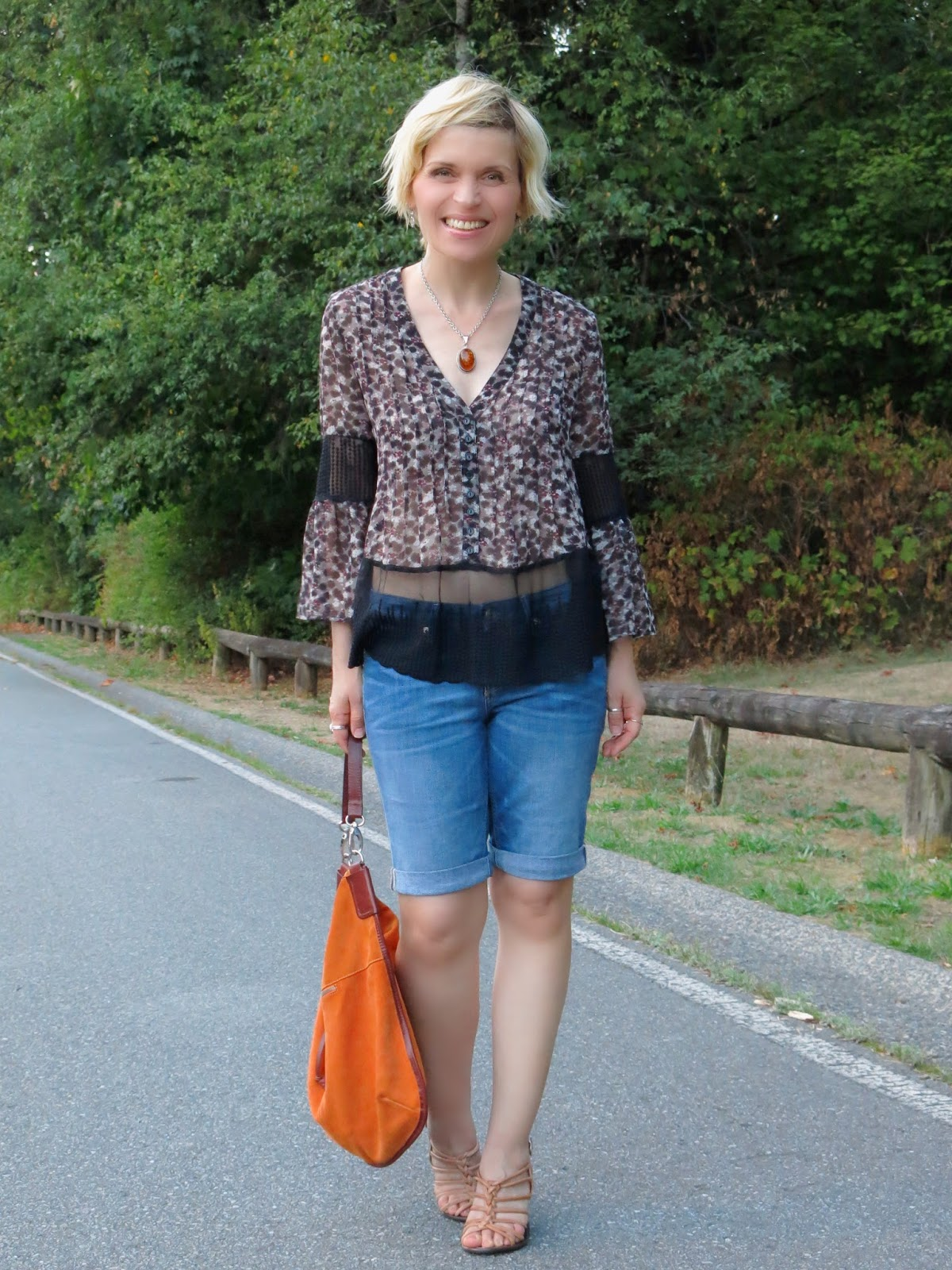 styling a peasant blouse with denim bermuda shorts and strappy nude sandals