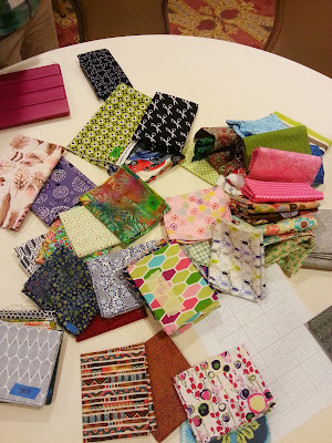 a bunch of folded fabrics laying on a table in a wide array of colors and patterns