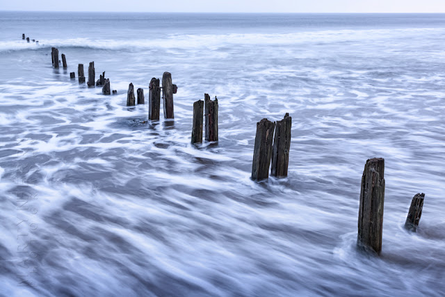 The ocean slips between the beach groynes at Sandsend by Martyn Ferry Photography