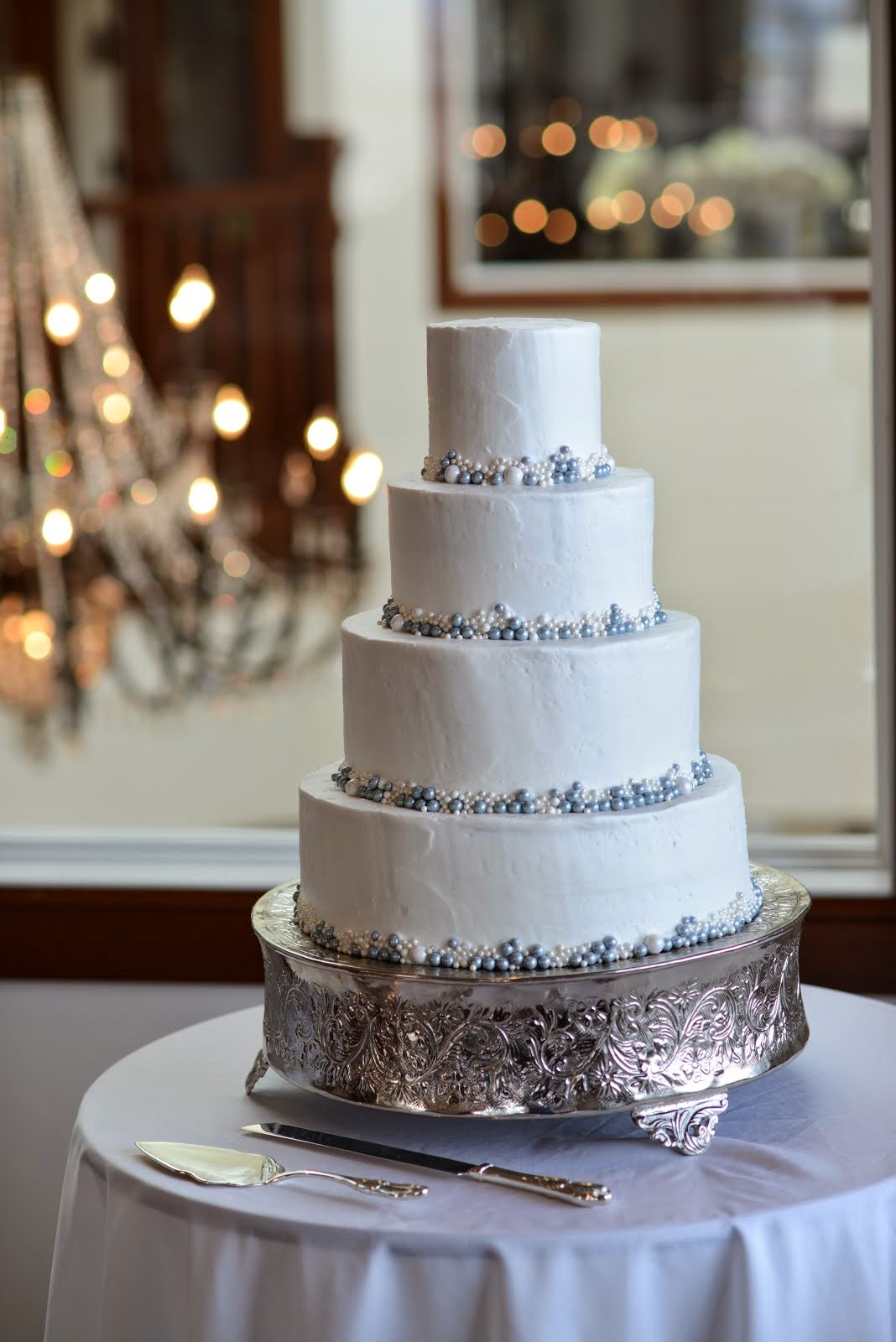 4-tier round buttercream with edible pearls