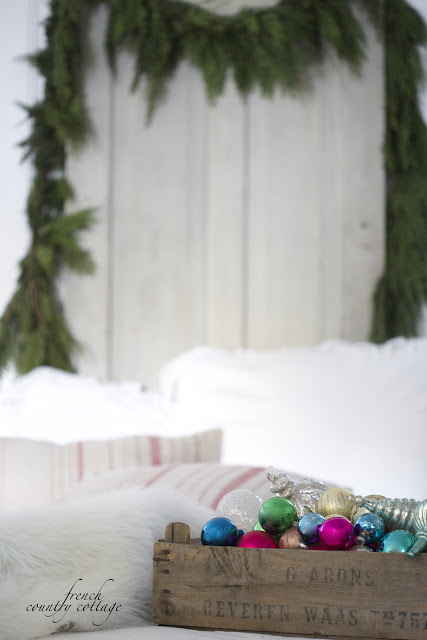 Fresh Garland on bed with ornaments in wooden crate
