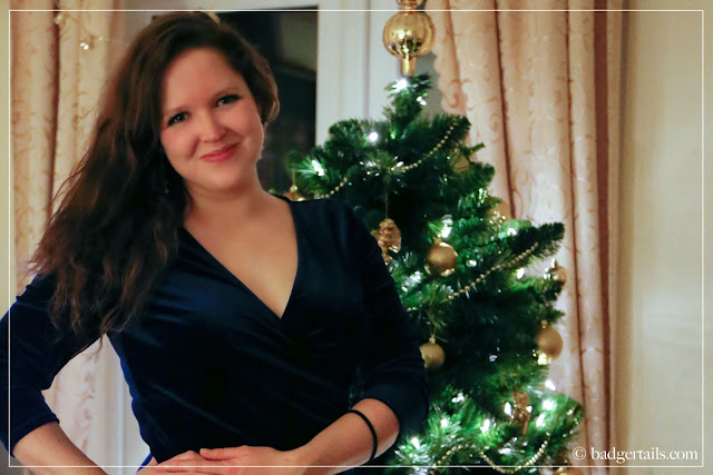 portrait of lady in navy velvet dress by christmas tree
