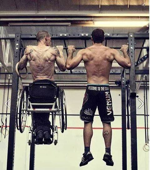 Two men viewed from behind doing pull-ups, man on the left is in a wheelchair