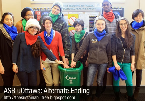 A group of students poses in front of a recycling bin