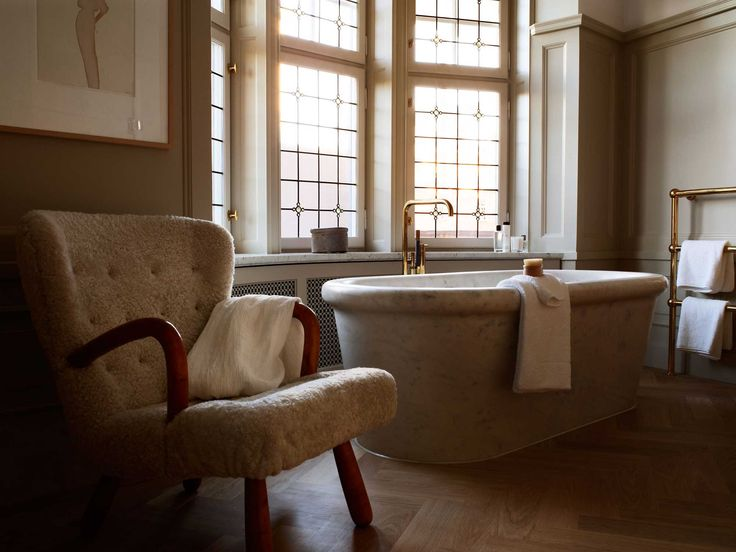 Marble bathtub with brass fixtures and midcentury modern chair