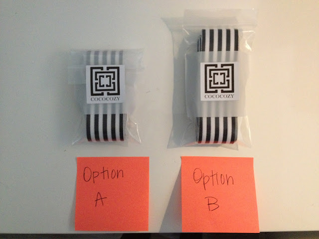 "Two black and white stripped ribbons folded neatly wrapped in plastic with COCOCOZY's logos on them on a white table. An orange post it note is in front of each stack with either ""Option A"" or ""Option B"" written on it"