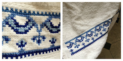 A set of three towels, one large bath sheet and two hand towels with aida border embroidered with cross stitch motif in different tones of blue, perfect for a modern bathroom