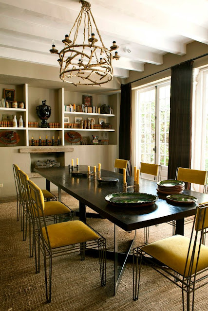 dining room from casamid facebook with yellow chairs, a fireplace, built in bookshelves full of books and small sculptures, floor length curtains, french doors and a wood chandelier light