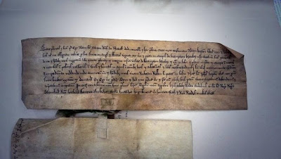 An old document, brown and irregular, with eight lines of dark old fashioned writing, it is attached by the tab for the seal to another document which is turned face down