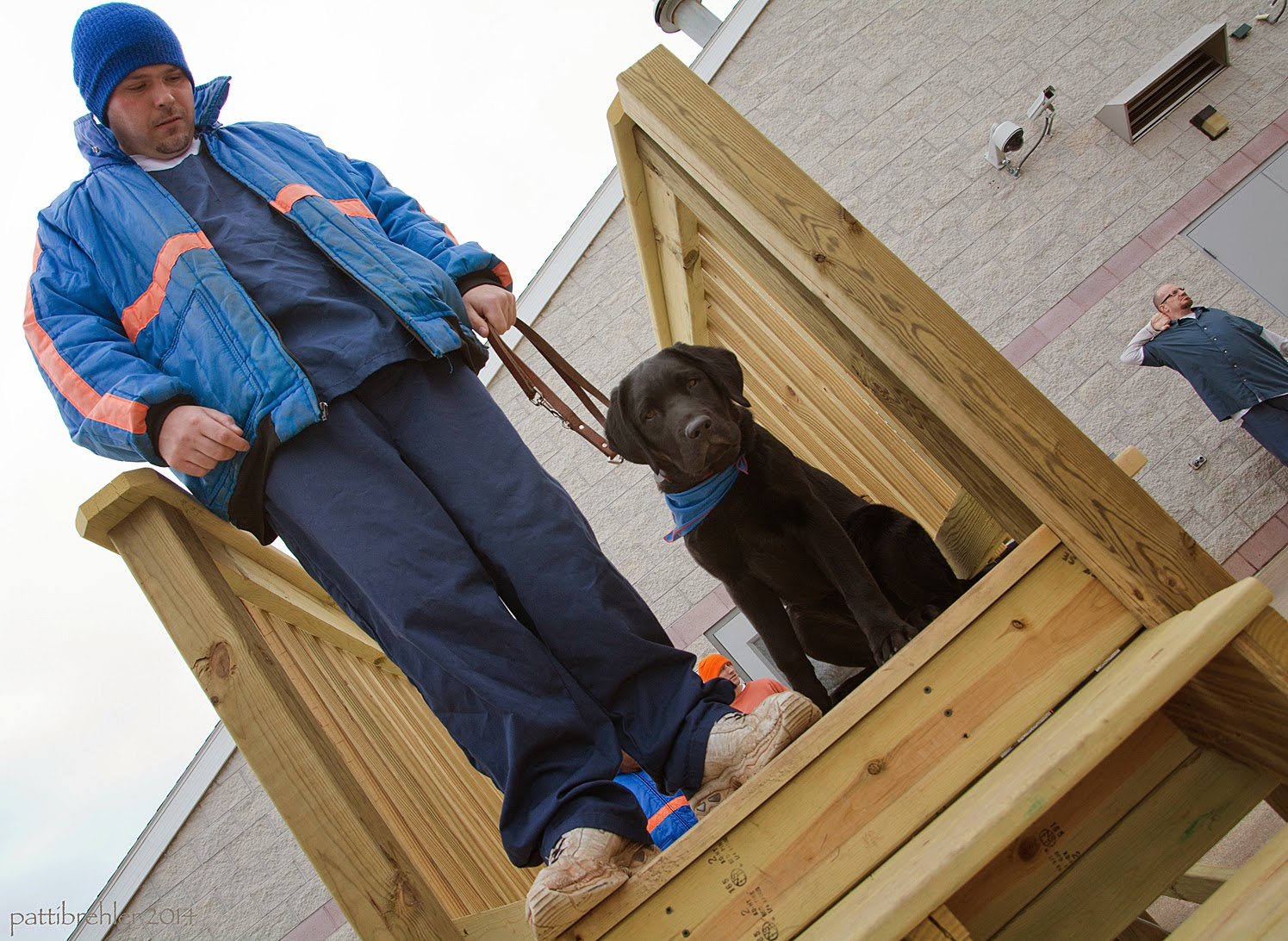Taken from an angle from below, a man dressed in the blue prison uniform with a blue stocking cap stands at the top of the wooden stairs. He is holding the leash of a black lab puppy with his left hand. The puppy is sitting on his left side looking at the camera. The man is looking down at the puppy. The puppy is wearing the blue Futurel Leader Dog bandana. There is another man far in the background on the right dressed in blue, in front of a white brick building.