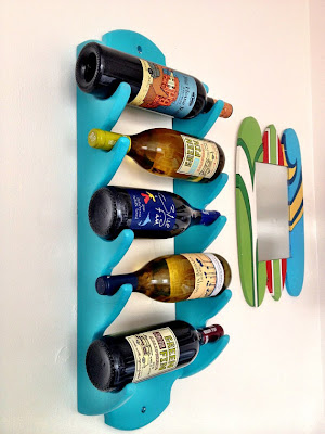 wall-mounted wine rack, aqua blue, holding 5 bottles