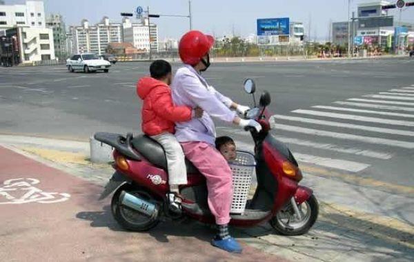 Criança andando de moto dentro de um cesto