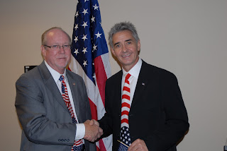 Jon Stettner (right) shakes hands with Charles Harrell, Acting Director of the USCIS Phoenix Field Office