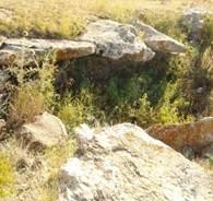 Расставленные, по краям одной из ям камни, образующие полукрышу