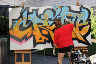 Graffiti Artist Ms. Reds using Black outline of sky blue and orange-yellow.