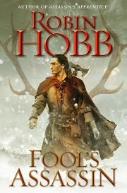 cover art for Fool's Assassin, featuring a pale-skinned man with long, dark hair walking through the snow. He has is head turned slightly to one side so he's in profile. He wears medievalesque leathers and carries an ax on his back. A large pair of antlers hover in the background.