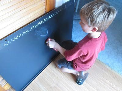 grandson writing on my old chalkboard