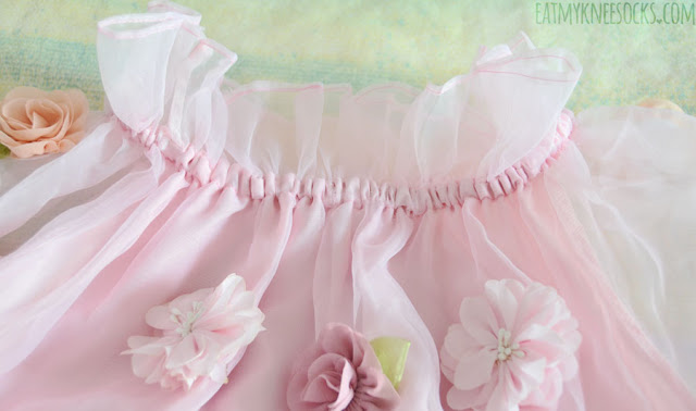 Close-up on the ruffled organza neckline and 3D applique fabric flowers on the Harajuku gyaru-style boat-neck dress from Romwe.