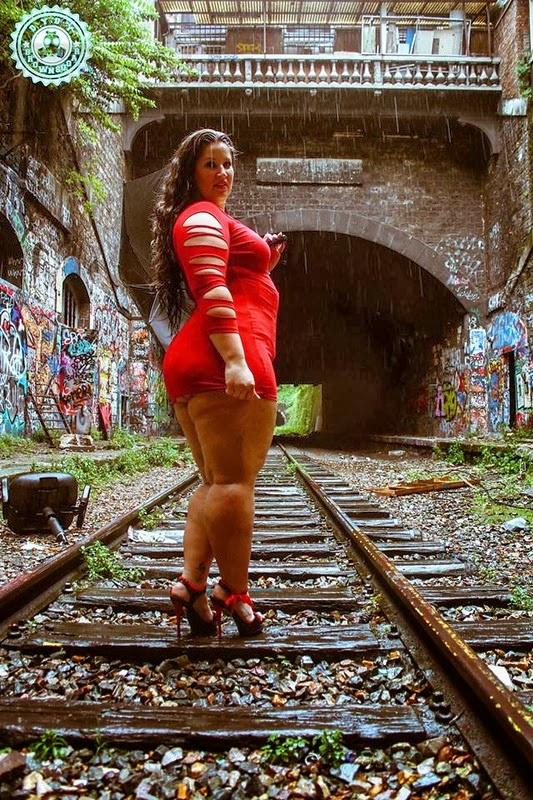 Lyna Sweet modèle BBW, sur la petite ceinture en talons et portant une robe rouge très sexy