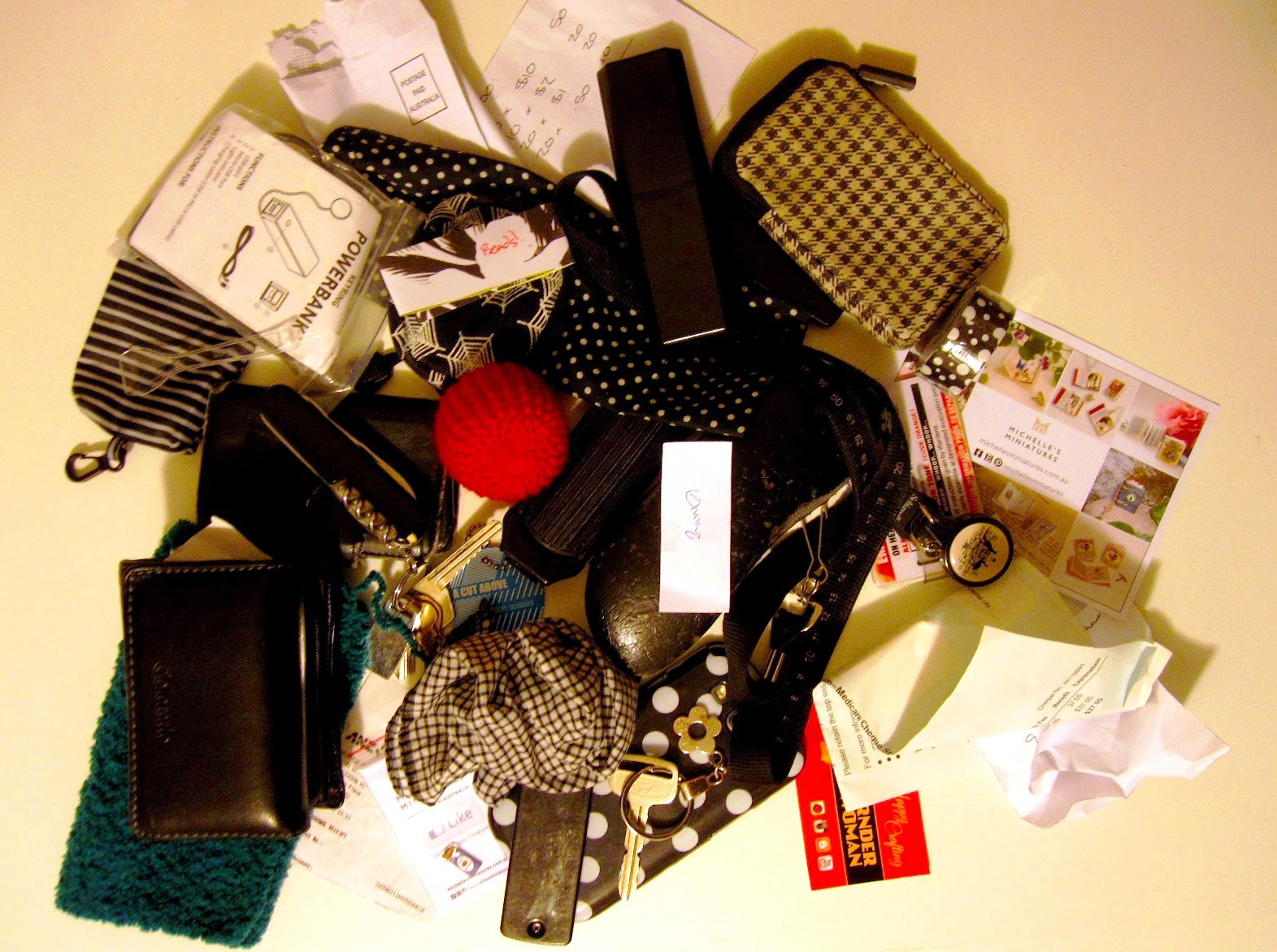 Large pile of items from a handbag including keys, hankie, wallet, various cases, business cards, scrunched up pieces of paper and a dolls' house miniature knitted pouffe and rug.