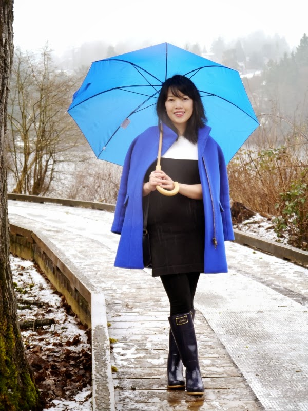A cobalt blue cocoon coat brightens up a black-and-white colour-blocked sweater dress and navy rain boots.