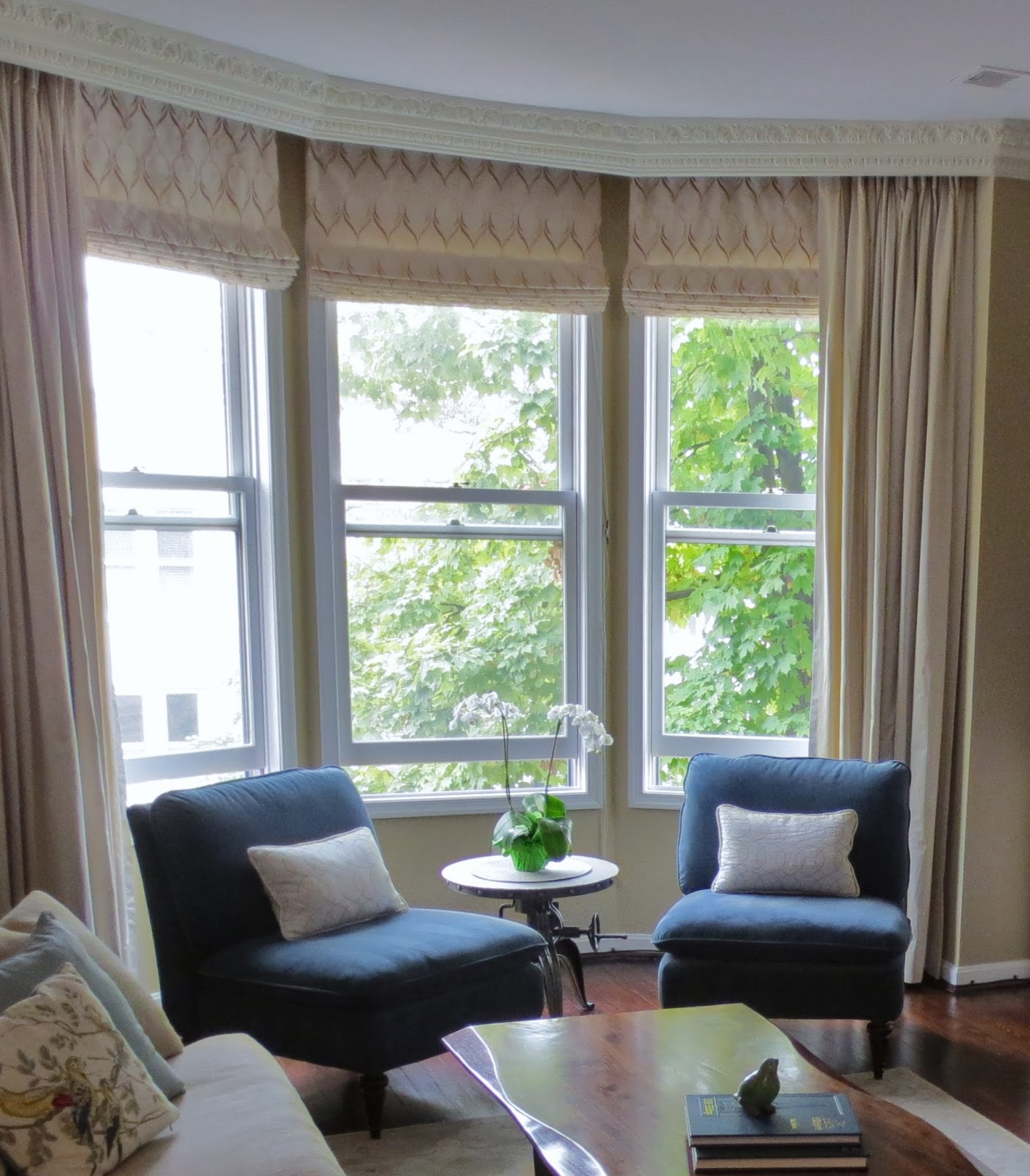 row house refuge a transitional living room heidi reused the roman shades left behind by the former homeowners and had drapes from an upstairs bedroom remade for the elegant bow window