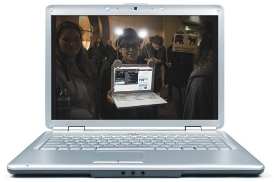 Person in crowd holding laptop computer