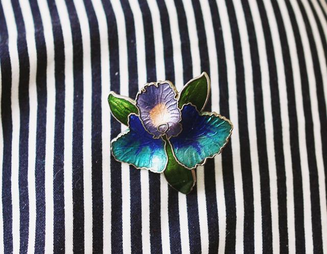 flower brooch on striped skirt