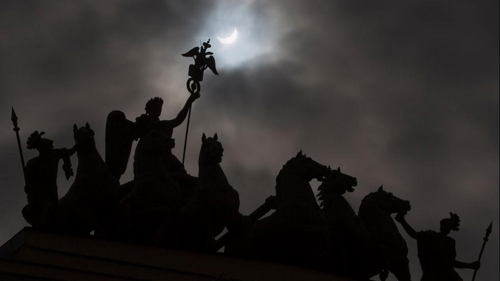 Луна частично закрывает Солнце над статуей  здания Главного штаба в Санкт-Петербурге, Россия.