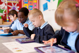 kids in classroom using ipads