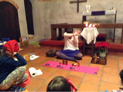 This is a modern-day photograph of a medieval chapel. A woman is seated on cross-legged on the floor, in front of the altar rail, facing away from the altar (towards the camera). She is wearing a white shirt, a purple skirt, and grey tights. She is white and has brown hair. There is a long narrow purple cloth on the floor in front of her, Among the objects laid on this cloth are some wooden figures from a Nativity Set (others are on a tray to her left). The woman has covered her eyes with her arms, as if to shield them from a bright light. Also in the photo are: a boy on the floor facing the Storyteller. He is wearing a Christmassy red stocking cap. We can just see the back of the head of a girl wearing a ribbon in her hair (facing the Storyteller) and the very edge of the face of a boy on the right also facing the Storyteller. In the left of the picture we also see, on the floor, a roll of paper towels, several baskets, and at least one piece of paper and some crayons.